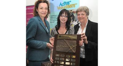 Trish Poole from Midcounties Co-operative, sponsors of the award, presents the trophy to wining student Jodie McCaughan, with Active Volunteers Co-ordinator Pat Green looking on.